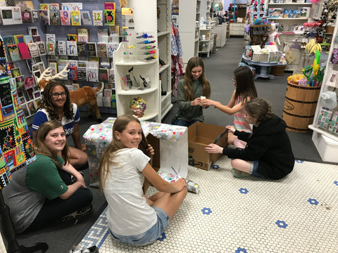 girl scout troop wrapping boxes to collect pet donations in periwinkle