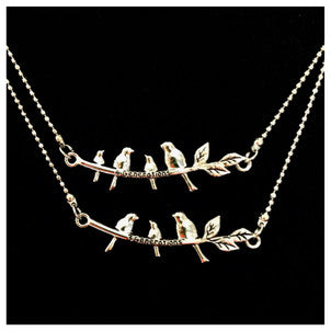 a picture of two necklaces on a velvet background. One is a branch with three birds. The other is a branch with four birds. Both necklaces are silver tone metal.