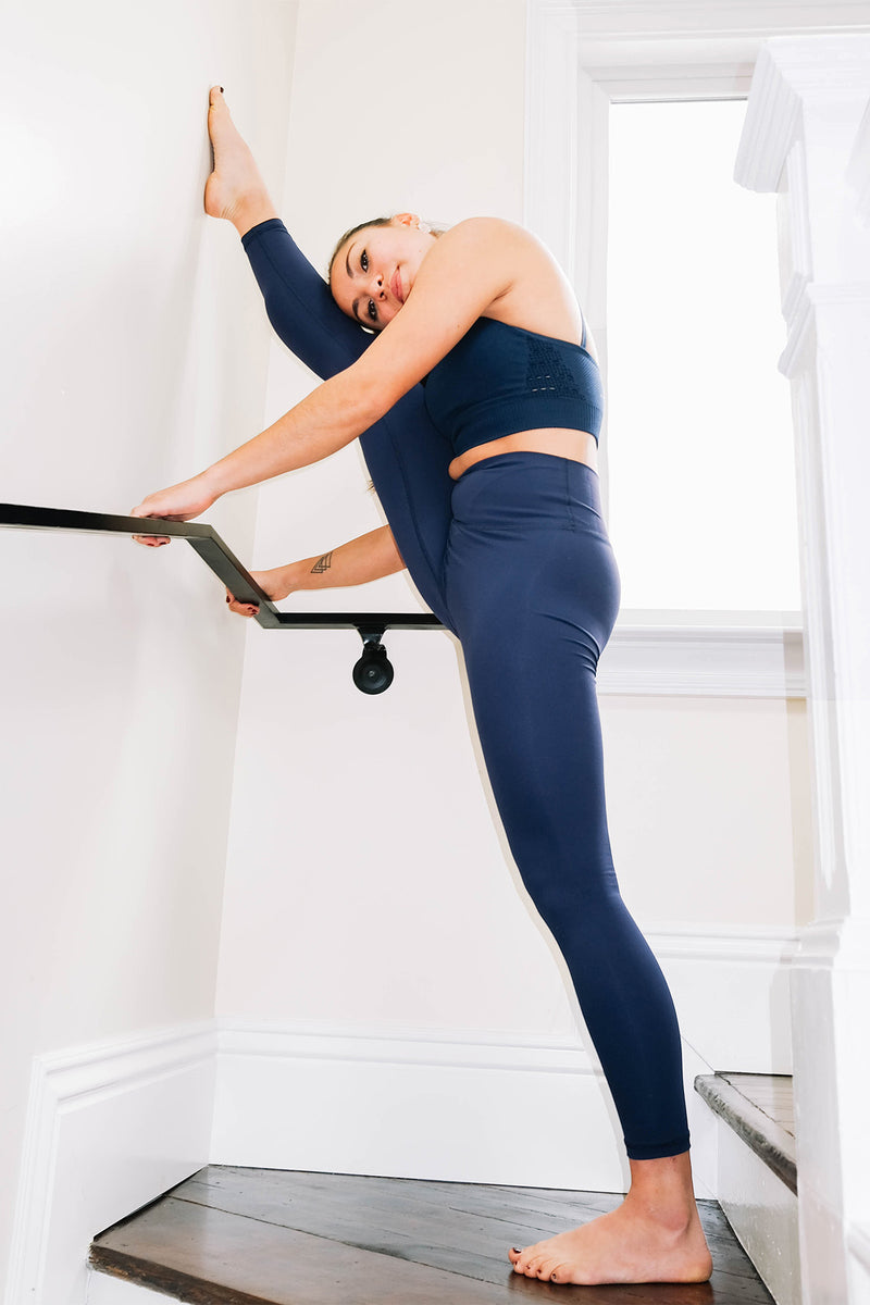 A fitness woman wearing a set of navy blue color wireless halter sports bra and Lululemon Align style high-waist seamless leggings doing stand split yoga pose