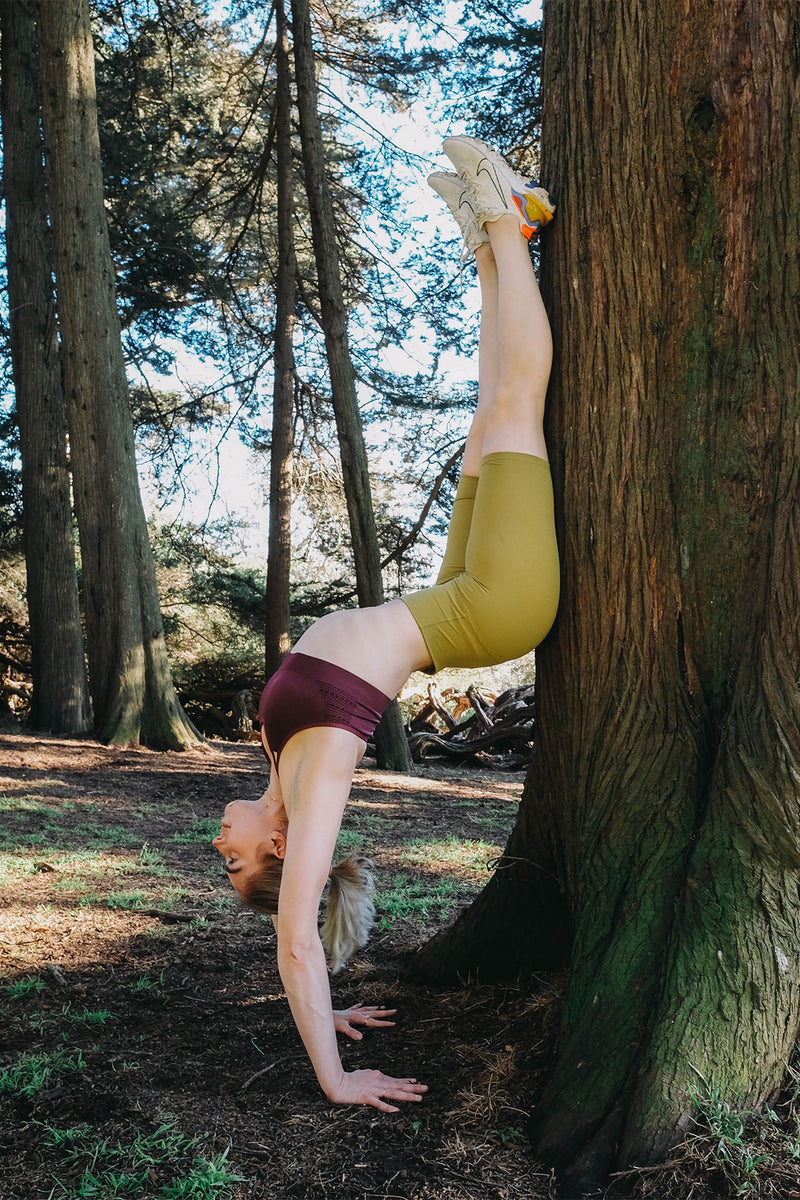 A women yogi is doing hand stand against the tree in the jungle wearing a mustard color high-waist seamless biker shorts, purple color halter sports bra and Nike sneakers.
