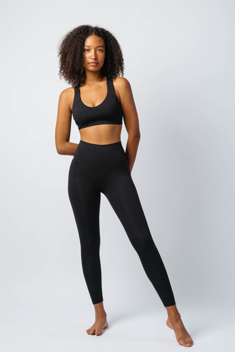 A black fitness woman wearing a set of black wireless sports bra and Lululemon Align style black high-waist seamless leggings with a confident look