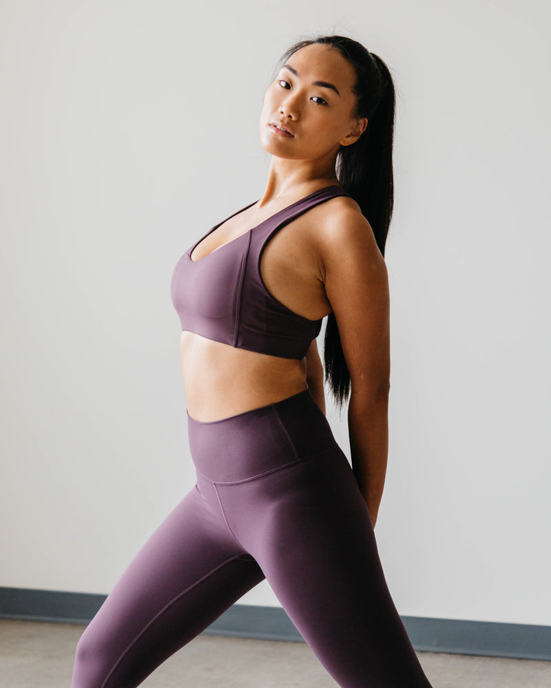 A fitness woman wearing a set of purple color wireless sports bra and Lululemon Align style high-waist seamless leggings doing stretch