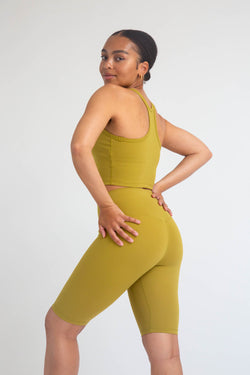 A black fitness model showcasing the back design of a mustard crop tank top and mustard color high-waist seamless biker shorts