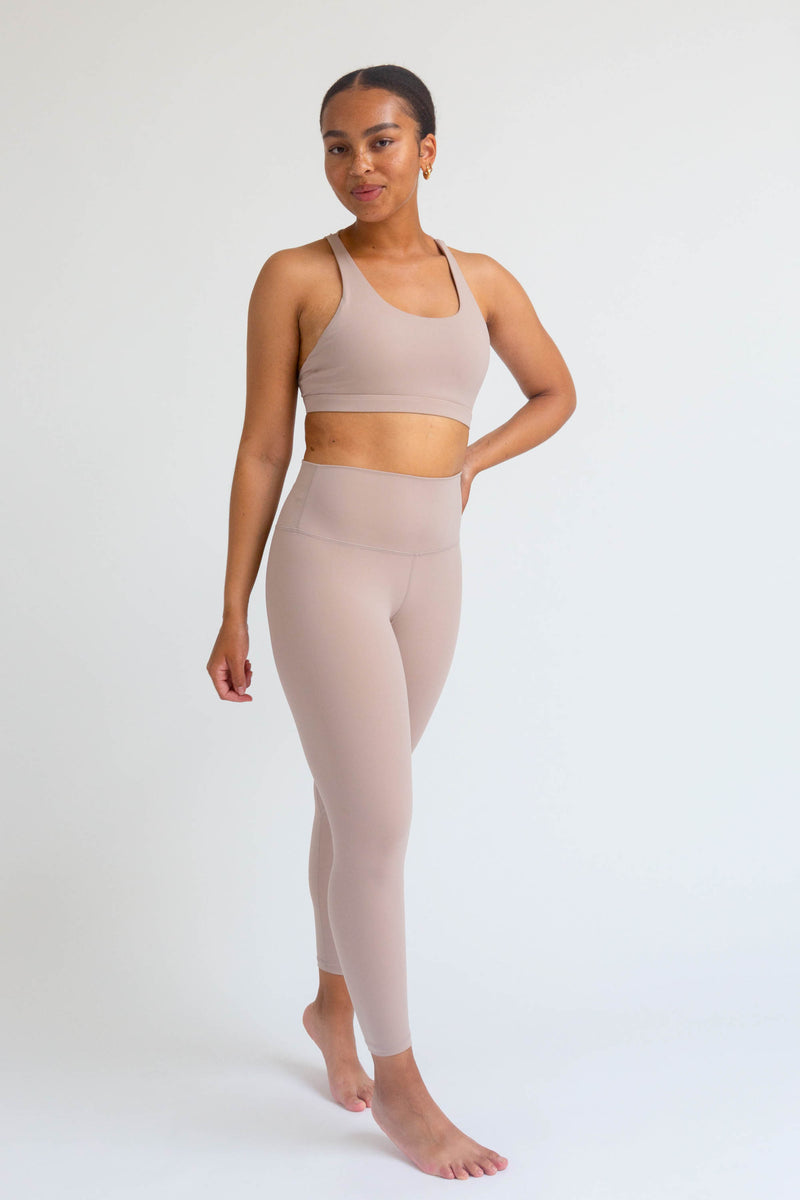 A black fitness woman wearing a set of nuddy sand color wireless sports bra and Lululemon Align style high-waist seamless leggings