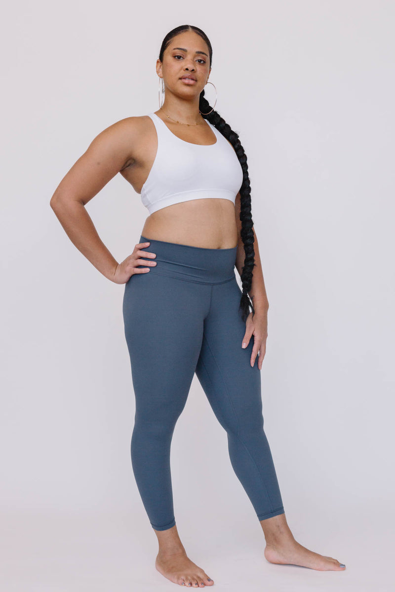 A black fitness women model wearing a white halter sports bra and Lululemon Align style grey color high-waist align seamless leggings with a confident look