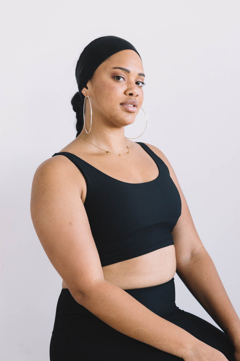 A black fitness woman wearing a set of black ribbed knit yoga bra and leggings, with a black soft modal wide headband plus two big ear loops to show a chic and confident workout look