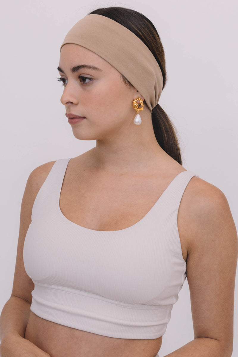 A gorgeous young fitness woman wearing a set of ivory color ribbed yoga bra and leggings, with a beige color, soft modal wide headband and vintage earrings to create a chic and elegant workout look