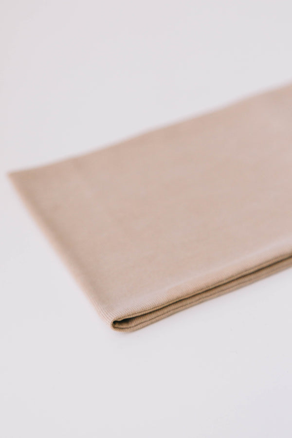 A close-up product shot of a beige color, soft modal wide headband to clearly show the detail of softness of the product