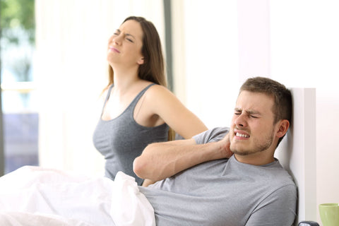 couple in bed with back pain and neck pain need new mattress