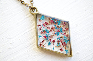 Real Pressed Flower and Resin Moon Necklace in Blues, Pinks, and Whites.