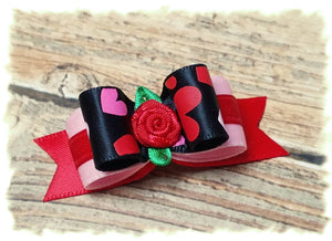 Hearts on black satin ribbon with red flower