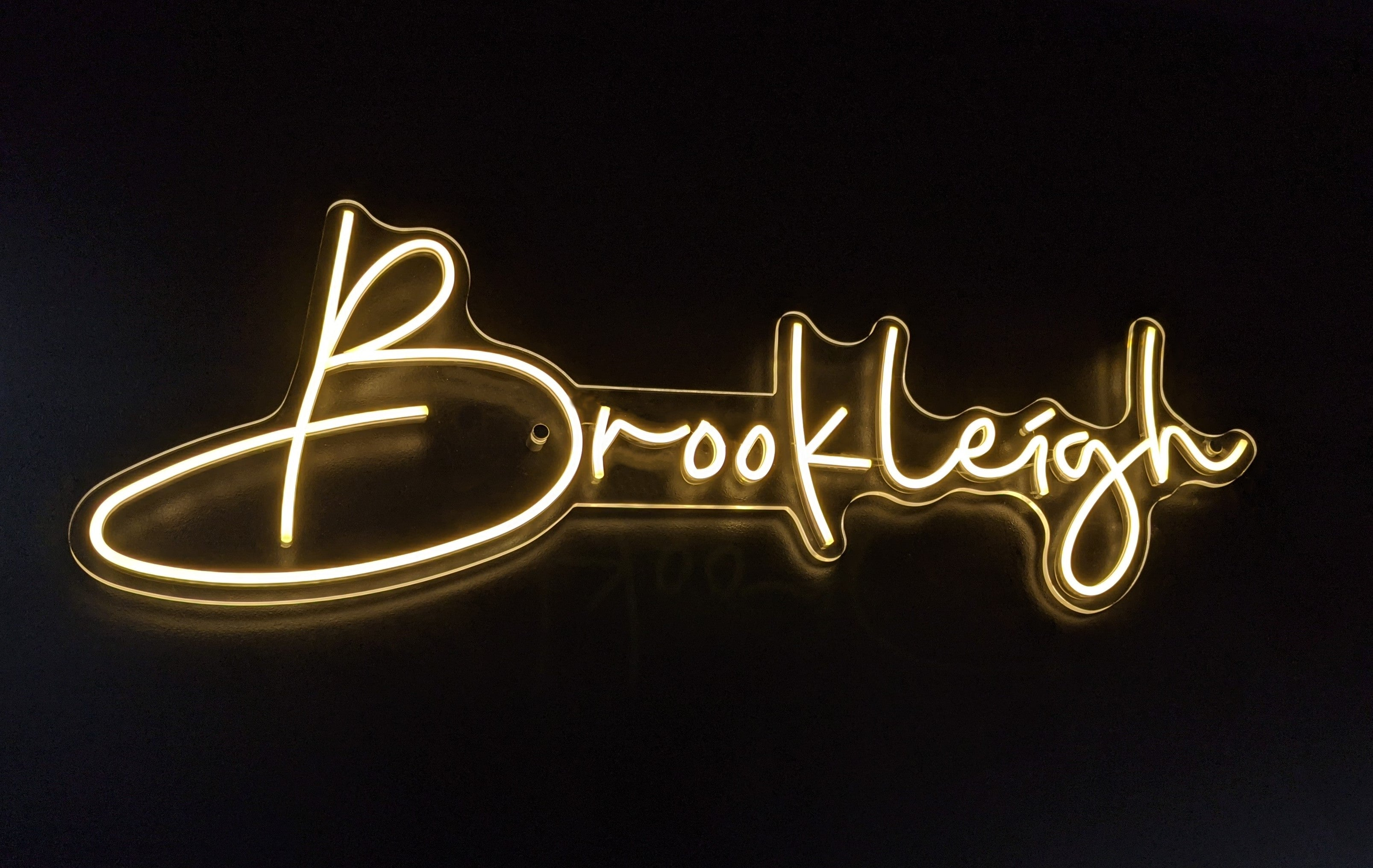 Brookleigh warm white neon sign wall mounted. Complimentary wall standoff mounts to install the beautiful neon light.