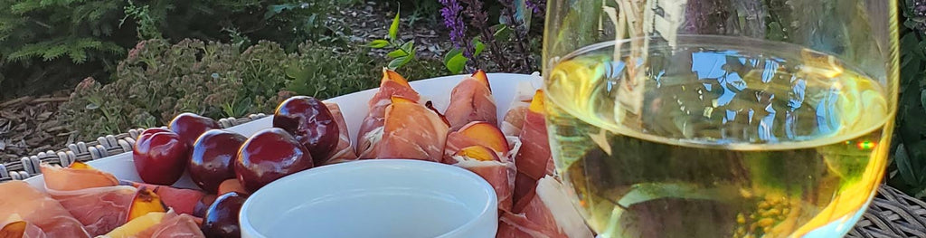 prosciutto wrapped grilled peaches and a glass of white wine