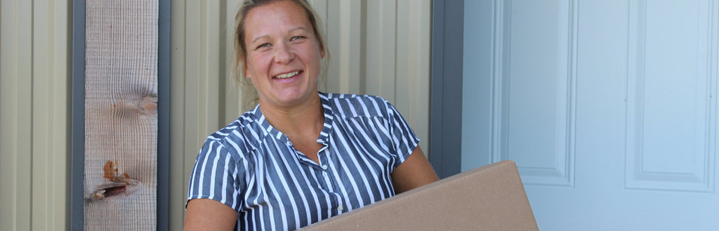 Woman smiling in striped shirt holding medium sized box