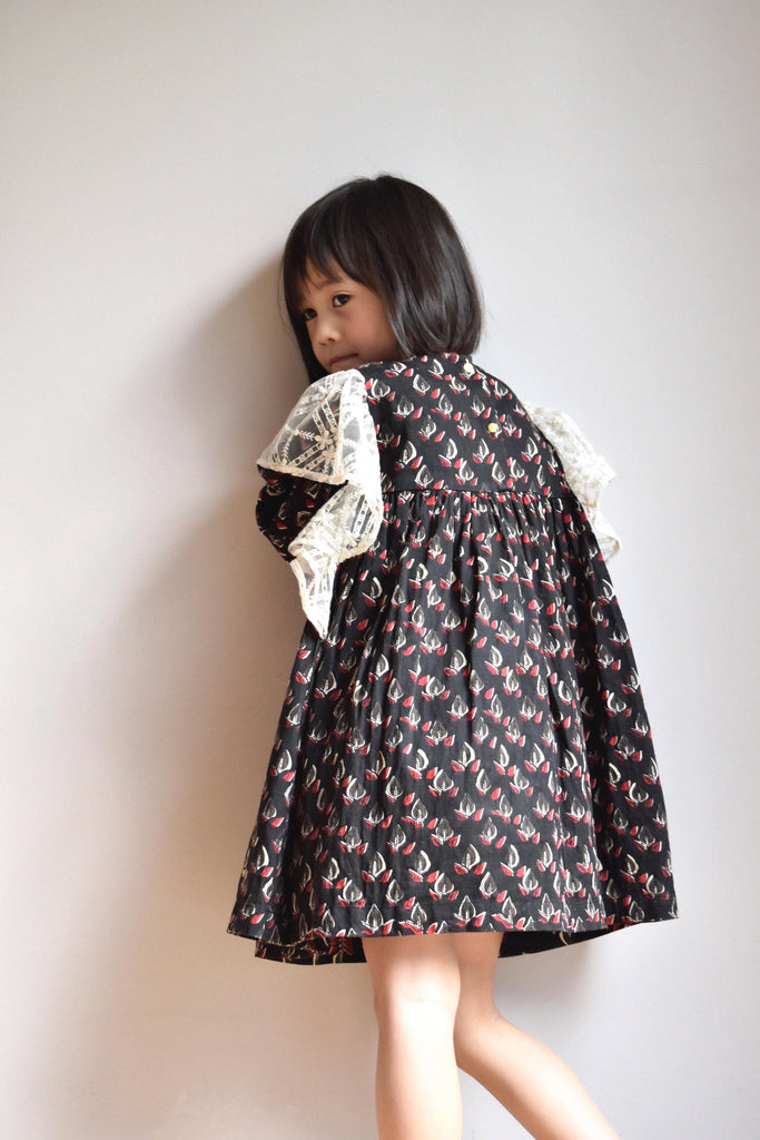 lulaland Fall No.15 Mirage collection. Girl wearing a black ruffled dress with leafy print and lace ruffles. Organic girl's clothes