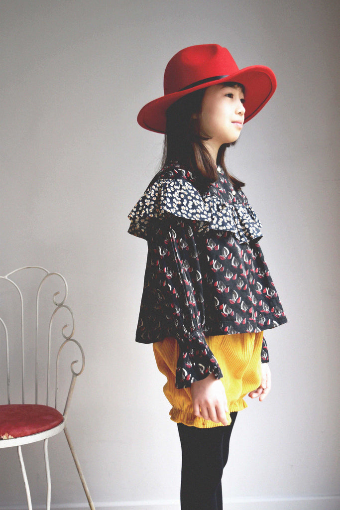 lulaland Fall No.15 Mirage collection. Girl wearing a black ruffled blouse with leafy print and yellow corduroy bloomers. Organic girl's clothes