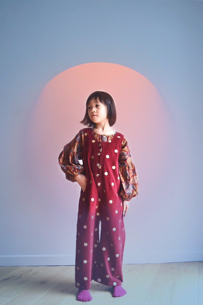 lulaland Fall No.15 Mirage collection. Girl wearing an oversized blouse with leafy print and polka dots red romper. Organic girl's clothes