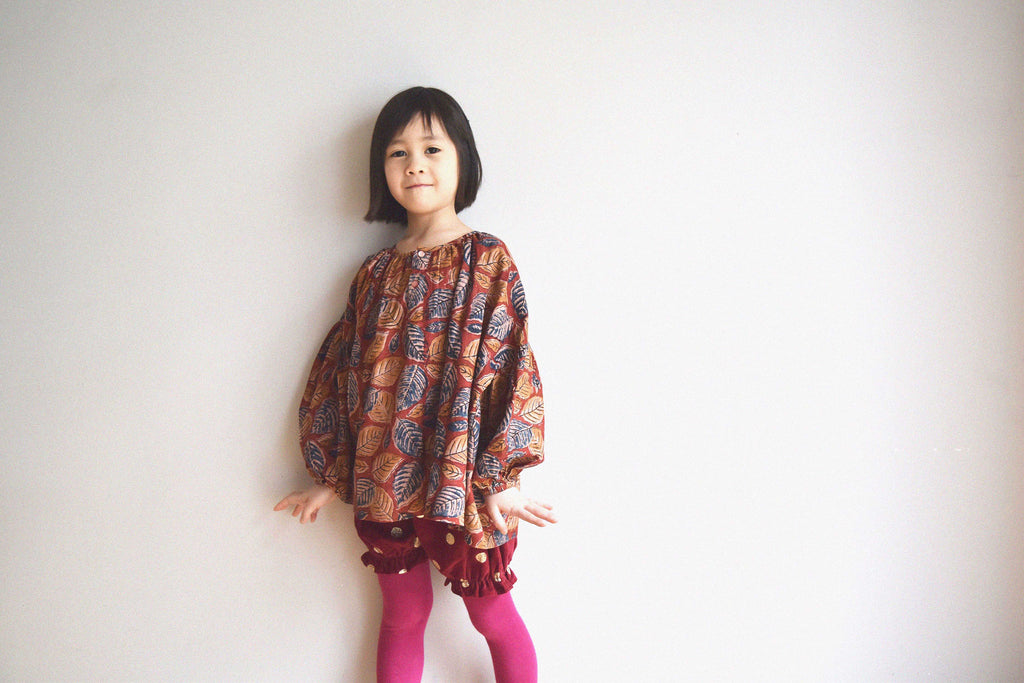 lulaland Fall No.15 Mirage collection. Girl wearing an oversized blouse with leafy print and polka dots red bloomers. Organic girl's clothes