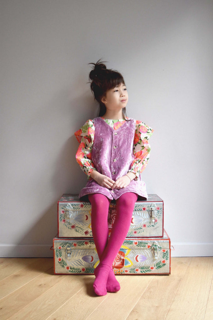 lulaland Fall No.15 Mirage collection. Girl wearing a flowery blouse and a lilac jumper sitting on adorned trunk