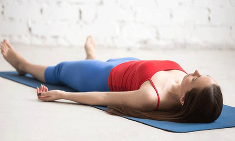 A woman lies on the floor on a yoga mat in Shavasana pose