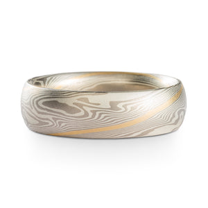 Mokume Gane ring or wedding band made by arn krebs, this ring is 6mm wide and has a low dome profile, it's made in our twist pattern and ash palette. The ash palette is palladium and sterling silver, and this ring also has an added yellow gold stratum that runs through the center of the pattern, twisting diagonally around the ring