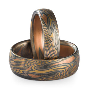 A set of Mokume Gane rings or wedding bands made by Arn Krebs, one is laid down flat on the surface, the other is propped up perpendicular inside the first. The rings are made in our twist pattern and firestorm palette, this palette is palladium silver red gold and yellow gold, both rings have low dome profiles