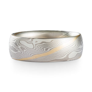 Mokume Gane Ring or wedding band, made by arn krebs, this ring is made in our twist pattern and ash palette, with a 14k yellow gold stratum added in and running through the center of the twist pattern diagonally through the ring, the ash palette is made up of palladium and sterling silver, this ring has a satin finish and low dome profile