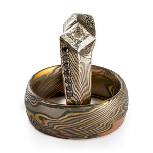 Set of rings, Mokume Gane, custom made, ring laying flat is a plain band, ring propped upright is a custom cathedral style setting with a large white center diamond flanked by rows of black diamonds bead set, both rings are firestorm palette and twist pattern
