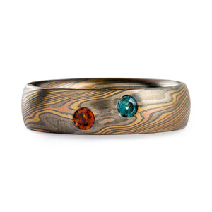 Mokume gane ring made by Arn Krebs, Firestorm palette and twist pattern. Low dome profile, and two 3mm stones flush set in, the stones are blue and orange. The ring itself is 6mm wide