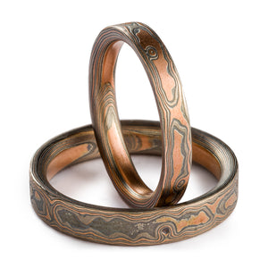 Mokume Gane ring set, woodgrain pattern and embers palette. Embers palette is red gold palladium and silver, both rings are etched and oxidized and have a flat profile. One ring is laid flat on the surface, second ring is propped up vertically in it.