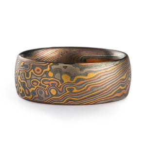 Mokume Gane ring made by arn krebs in a twist and droplet combination pattern. The ring is made of layers of red gold yellow gold and palladium with oxidized silver in between each. The ring is 7mm wide and has a low dome profile