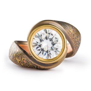 Mokume gane ring with a bypass style setting, the ring wraps itself around a large 9mm wide moissanite held in a gold bezel. The ring has a droplet pattern and the metals used are red gold yellow gold and silver.
