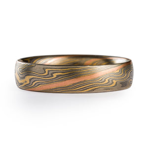 Mokume gane ring made by arn krebs, twist pattern with a red gold strip running diagonally across the ring, the rest of the ring is alternating layers of silver and palladium and yellow gold