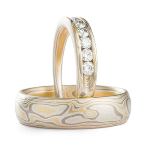 two mokume gane rings, one propped up while the other lies flat, upright ring has stones set into it, both rings are made of gold silver and palladium and have an overall light gray/yellow appearance. The patterning is meant to resemble the grain of wood