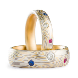 Matched set of mokume gane rings, made of yellow gold palladium non oxidized silver, both rings have 3 flush set stones each, a moissanite ruby and sapphire