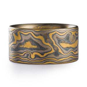 Woodgrain Pattern Mokume ring made by arn krebs, pattern resembles the texture of wood, and is made of alternating layers of yellow gold palladium and silver, the ring has been etched and oxidized and has a flat profile, it's a wider ring at 10mm