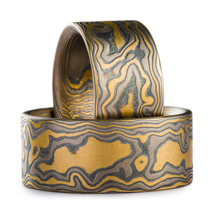 Set of Mokume Gane rings made by arn krebs, one ring is propped up inside the other one which is laid flat. Both are made in a woodgrain pattern and are made of layers of yellow gold palladium and oxidized silver