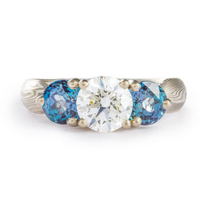 Emgagement style ring, 3 head prong setting in the center, a slightly larger round white diamond in the middle, two smaller blue gems on either side (alexandrites), prongs are white gold, the ring is an overall silver color, the mokume is made of silver palladium and white gold