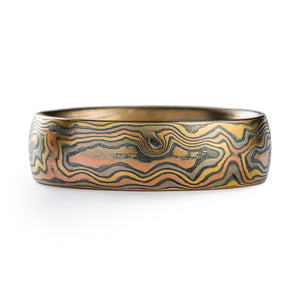 Mokume gane ring arn krebs, wedding band or ring, woodgrain pattern and firestorm palette, firestorm metal combination is red gold palladium silver and yellow gold, yellow gold is most prominent in this ring  Edit alt text