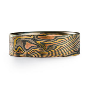 Mokume Gane ring made by arn krebs, twisting pattern that runs diagonally across the ring, ring is multicolored, made of layers of palladium, yellow and red gold alternating with oxidized sterling silver