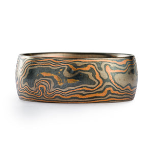 Mokume gane band or wedding ring made by arn krebs, this ring is made in our woodgrain pattern and embers palette. Our embers metal palette is made up of red gold, palladium and sterling silver, and the red gold is the dominant color. The ring is 8.5mm wide and has a low dome profile.