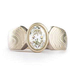Unique modified cathedral style ring with mokume gane patterning, the main band is split in the center with gently curved ends, and is holding an oval bezel with a diamond that is the same height as the band. The ring is overall silver and white