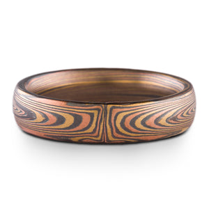 mokume gane band in vortex pattern oxidized fire palette, red gold yellow gold and oxidized silver layers form an asymmetrical pattern meeting at the center of the ring, on a white background