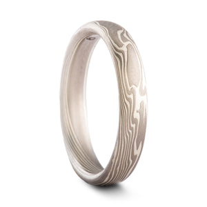 Mokume gane ring made by arn krebs, patterning is made up of alternating layers of silver and palladium, the pattern resembles flowing smoke, twisting and rippling in a diagonal direction around the ring