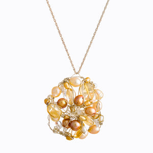 Pendant hanging on a silver chain, made by Susan Freda, champagne colored pearls of varying shades interwoven with champagne translucent beads, held together with twisted wire