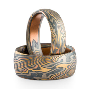 Mokume gane matching ring or wedding band set made by arn krebs, 6mm and 9mm widths, both rings made in firestorm palette and twist pattern, red gold yellow gold palladium and sterling silver