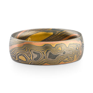 Mokume gane ring or wedding band made by arn krebs, twist pattern and flare palette (yellow gold, palladium and silver) with an added red gold stratum running through the pattern, etched and oxidized finish