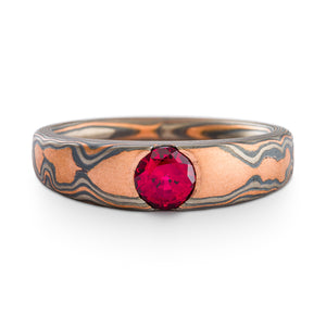 Mokume Gane ring or wedding ring by arn krebs with a cathedral style setting with a ruby, woodgrain pattern and embers palette, the embers palette is red gold palladium and silver, the ring is predominantly red gold
