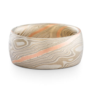 Mokume gane ring or wedding band made by arn krebs, 9mm wide band, twist pattern and smoke palette, the smoke palette is white gold palladium and silver, and this ring has an added red gold stratum layer running through the twist pattern