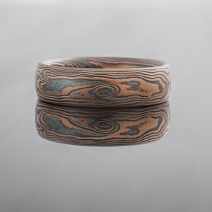 Rustic wedding ring Mokume Gane mens alternative metal Ring Wedding Band. Red rose gold, palladium and oxidized blackened silver alternative metal stylish fashionable unique mens wedding band silver black red topographical nature inspired wood grain pattern patterned